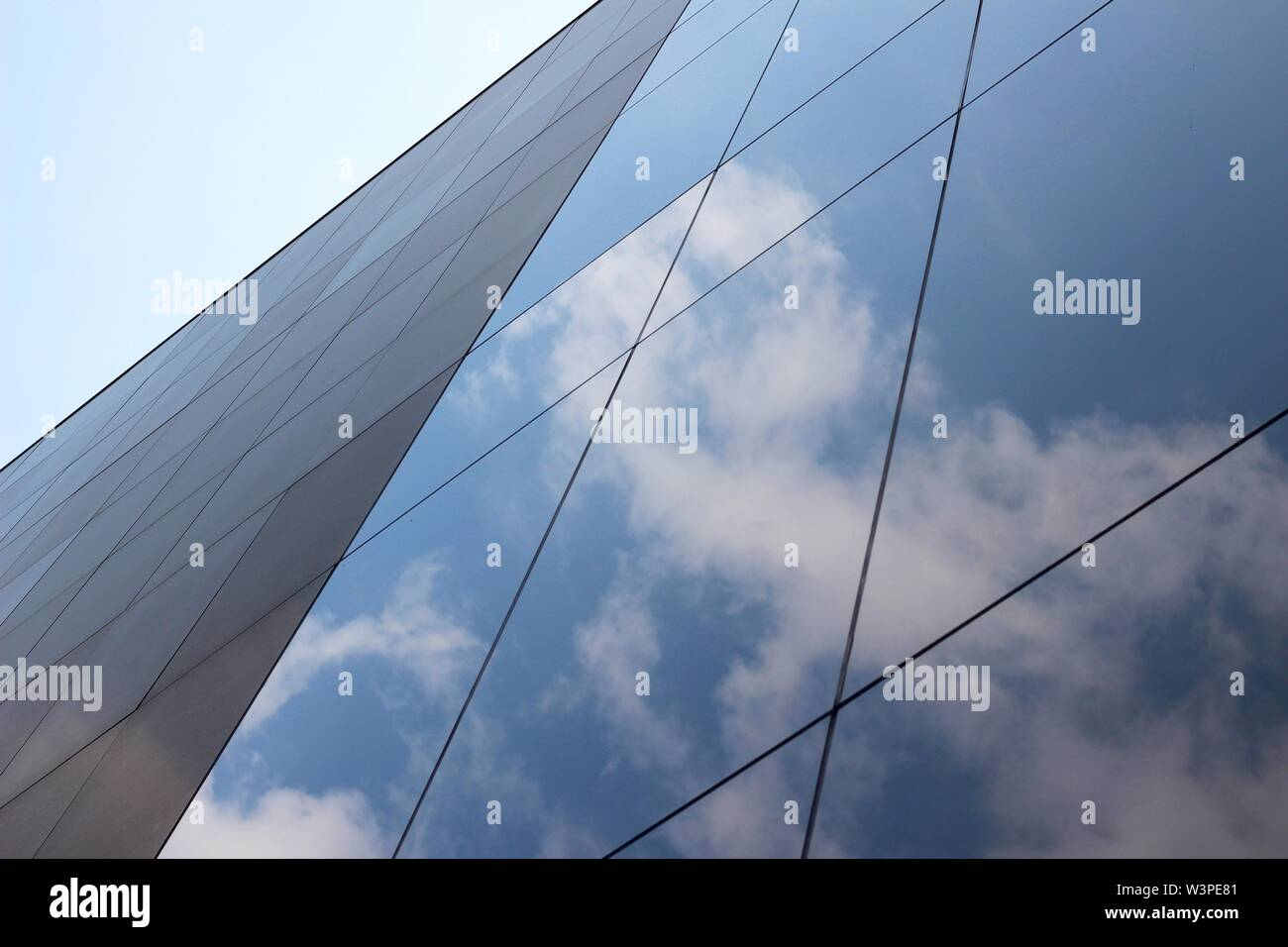 Un angle bas tourné d'un gratte-ciel en verre de bâtiment d'affaires avec un reflet de nuages et le ciel sur elle Photo Stock