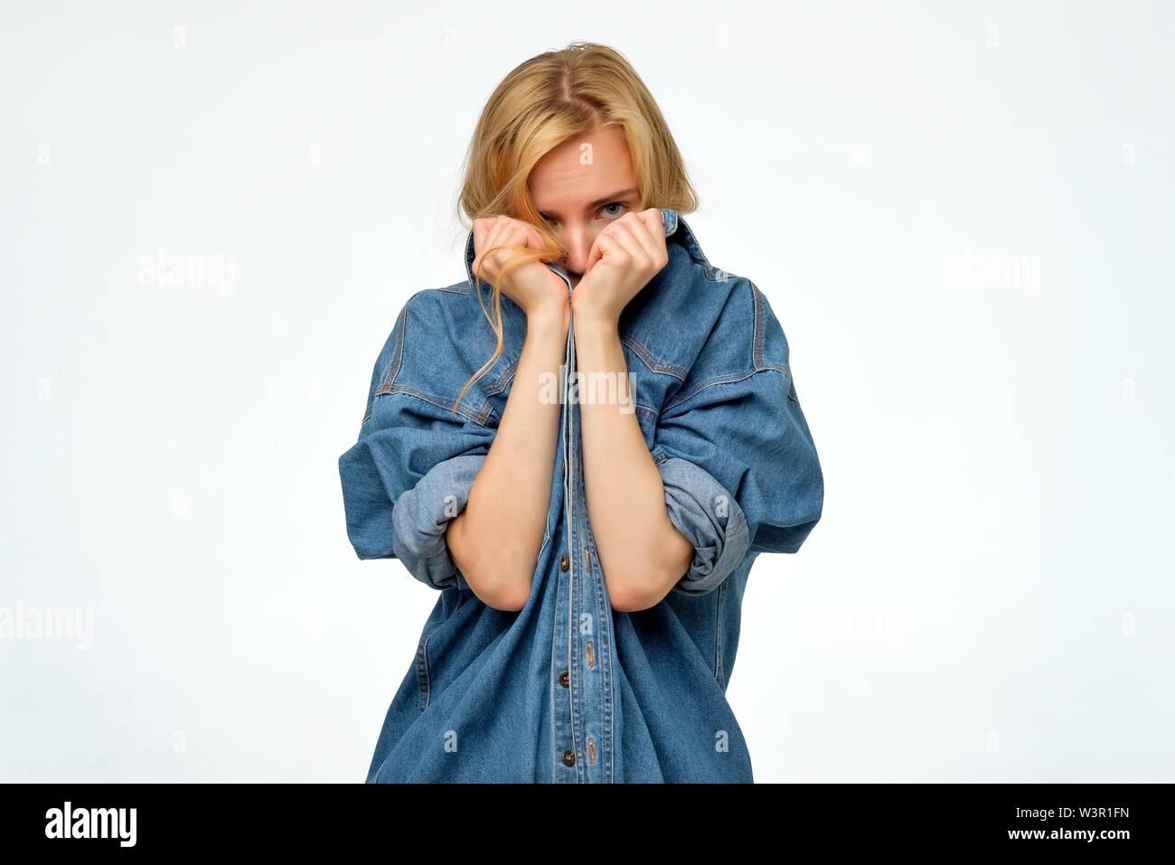 Femme en denim shirt r cachant son visage. Elle veut rester anonyme. Photo Stock