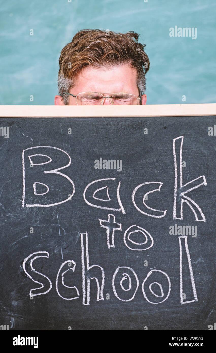 Préparer l'année scolaire. Êtes-vous prêt étude. Enseignant ou directeur d'école se félicite de l'inscription retour à l'école. Se cacher derrière l'éducateur tableau noir. Les possibilités d'éducation, de l'enseignant.tableau noir. Photo Stock