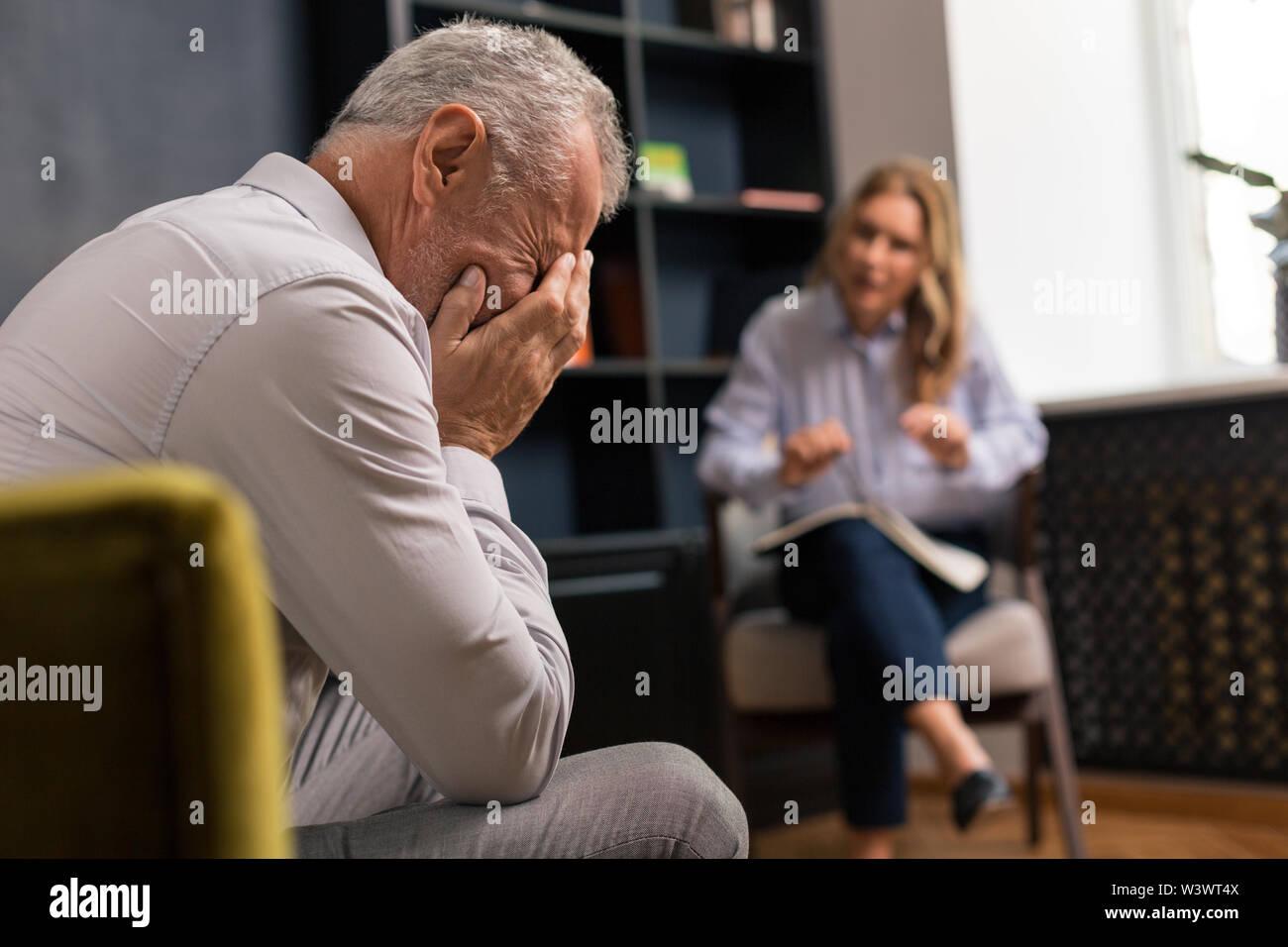 Cachant son visage. Déprimé homme aux cheveux gris couvrant son visage avec les mains pendant l'écoute d'une femme blonde assise à côté de lui Photo Stock