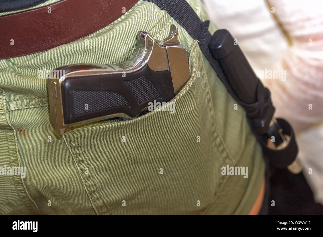 Pistolet dans la poche arrière du pantalon verdâtre Photo Stock