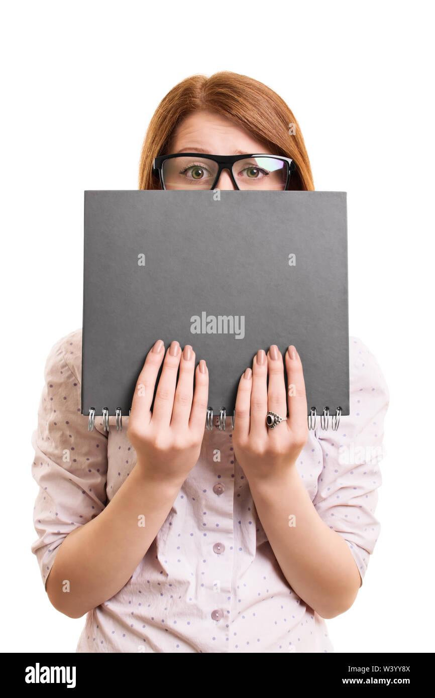 Le portrait d'une étudiante inquiète de se cacher derrière son livre, isolé sur fond blanc. Photo Stock