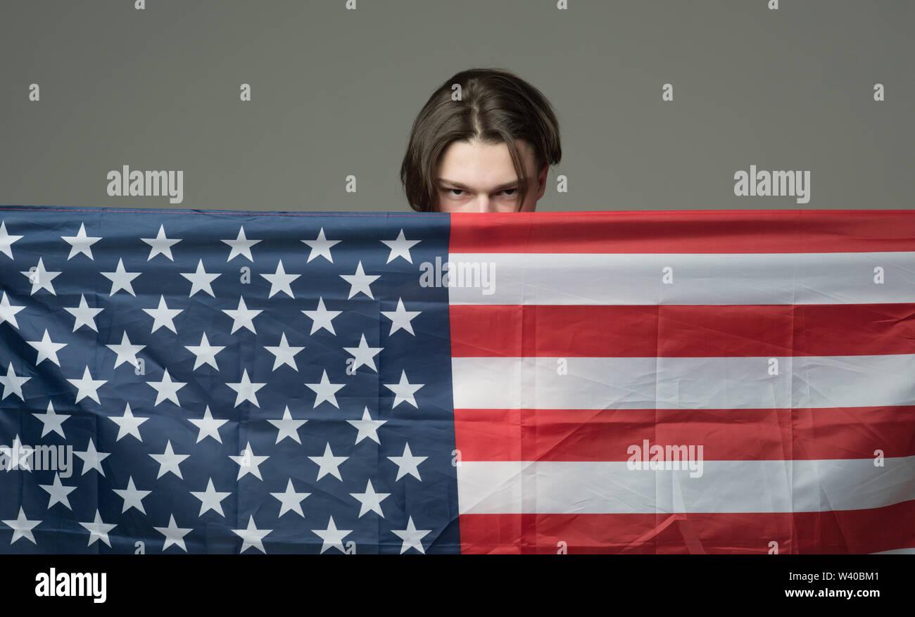 L'homme sur visage sérieux est titulaire d'un drapeau des Etats-Unis, se cachant derrière un drapeau. Guy se cachant dans des États-Unis d'Amérique, le protège, fond gris. La vie privée et de complot concept Photo Stock