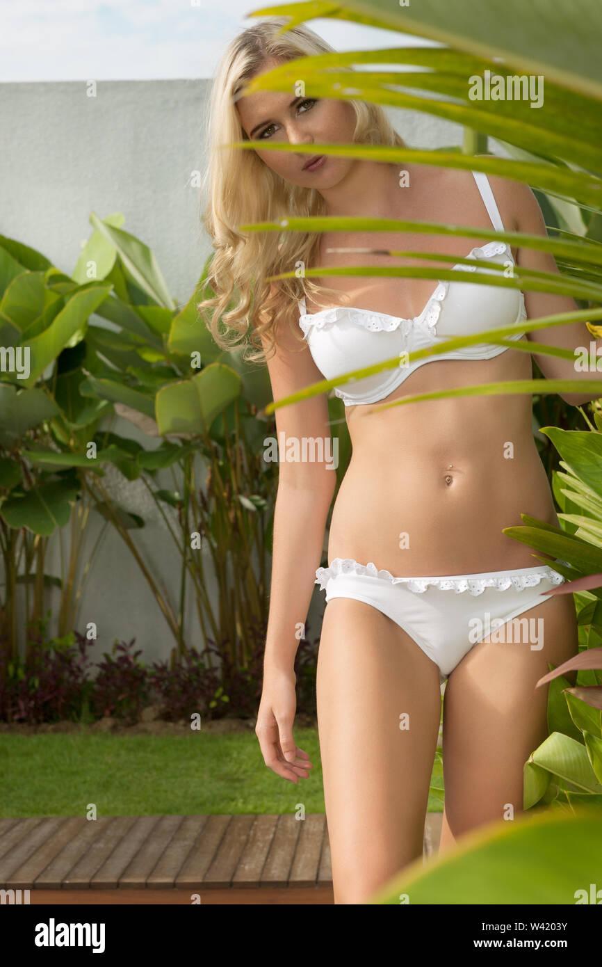 Blonde en bikini blanc se cacher derrière les plantes de jardin vert Photo Stock