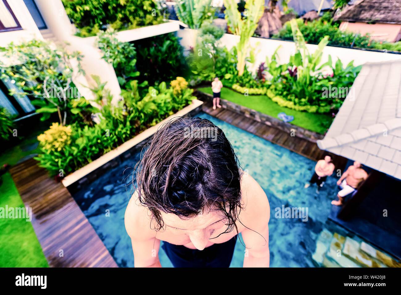 Woman climbing une échelle à côté de la piscine dans un hôtel de luxe avec l'arrière-plan flou Photo Stock