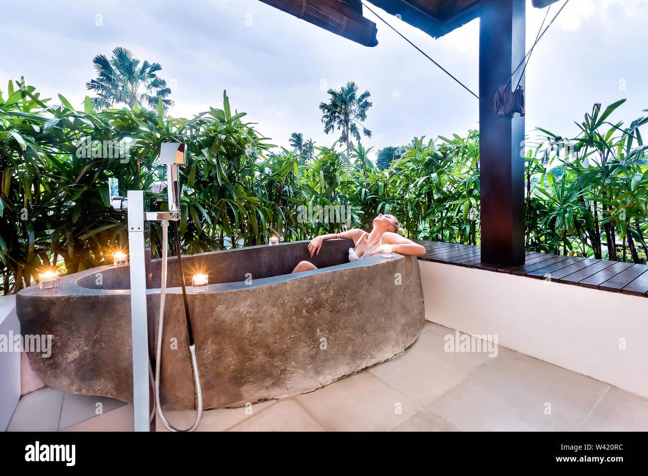 Jeune femme est de prendre un repos dans un bain à remous en pierre avec bougie clignotante autour d'elle et couvert de plantes vertes Photo Stock