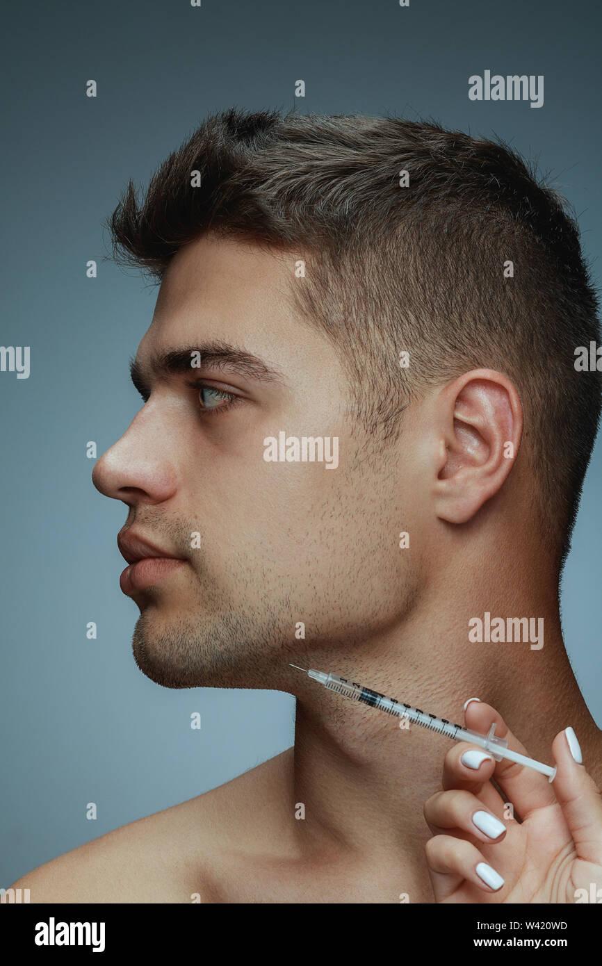 Close-up portrait of young man isolé sur fond studio gris. La chirurgie botox remplissage intérieur. Concept de l'Homme de santé et beauté, cosmétologie, auto-soins, soins du corps et de la peau. Anti-vieillissement. Photo Stock