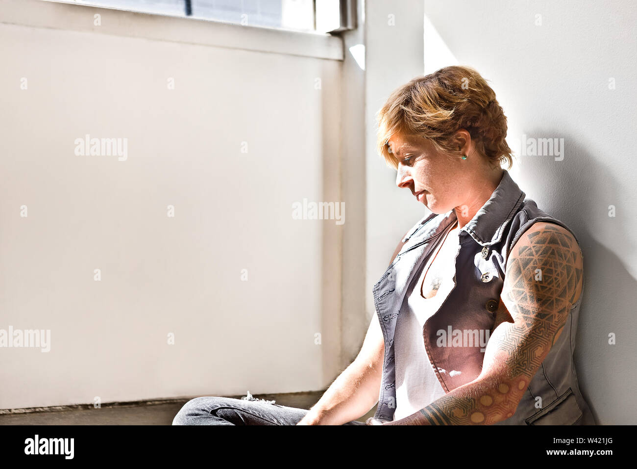 Femme avec un tatouage sur les mains souffrent d'un problème et d'essayer de le résoudre penser assis sur le sol au soleil dans une chambre Photo Stock