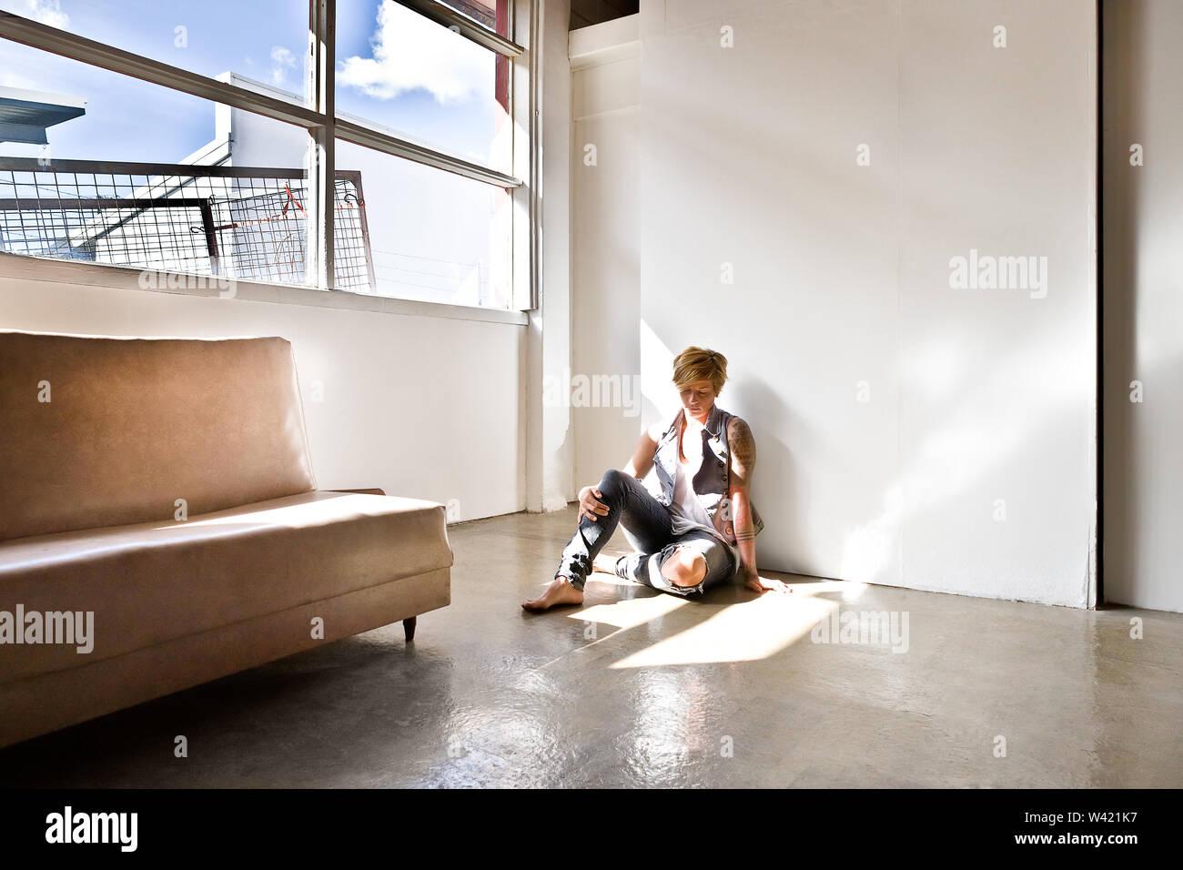 Femme avec un tatouage et cheveux courts assis sur le plancher avec un visage triste dans une chambre avec des rayons de soleil Photo Stock