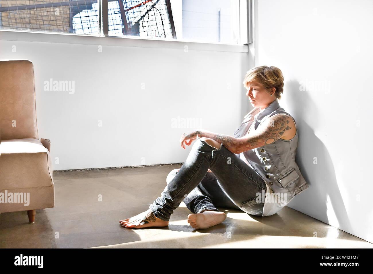 Jeune femme aux cheveux couleur d'or avec des tatouages sur le corps assis sur le plancher à l'intérieur d'une chambre, près de la fenêtre Photo Stock