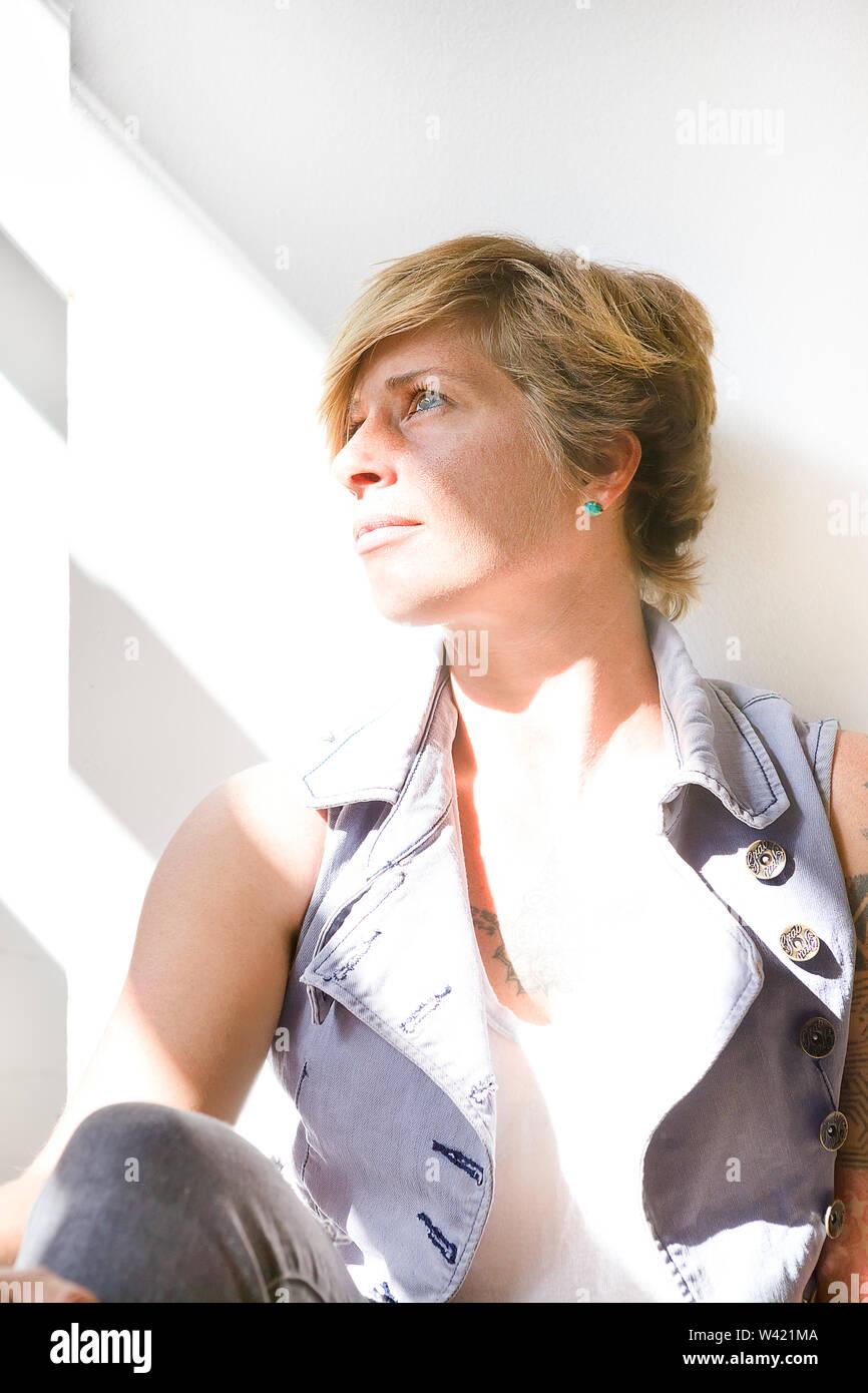 Jeune femme avec des cheveux courts et une assise à l'écart grâce à la lumière du soleil comme un souffrent d'un problème ou d'essayer de se détendre, gros plan Photo Stock
