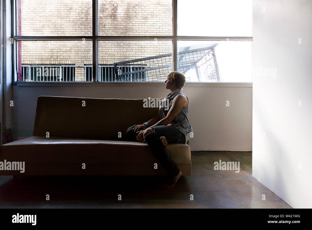 Jeune fille assise sur un canapé et détourner le regard de la fenêtre pour voir à l'extérieur dans une pièce avec des murs blancs Photo Stock