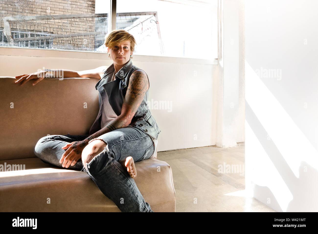 Belle femme avec un tatouage assis sur une chaise et à l'avant dans une chambre avec des murs blancs, à côté d'une fenêtre qui a montré l'extérieur Photo Stock