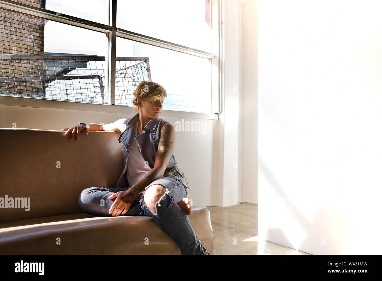 Jeune femme avec un tatouage assis sur un canapé dans une pièce sombre près de la fenêtre et un mur blanc, semble comme avoir un problème et la pensée Photo Stock