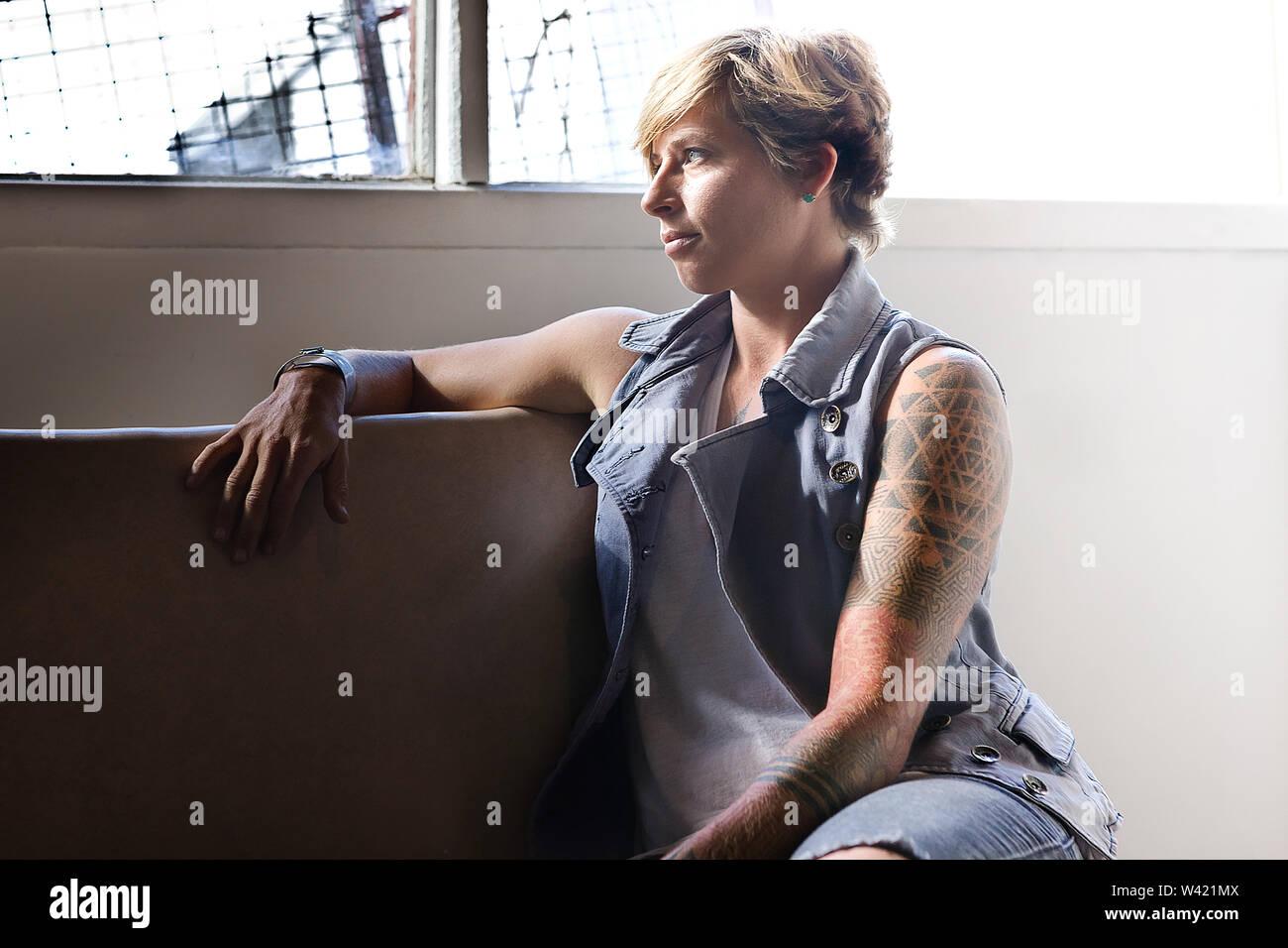 Fille aux cheveux courts avec tatouage sur sa main, assis sur une chaise et détourner le regard à travers la fenêtre montrant le comportement de réflexion sur un problème Photo Stock