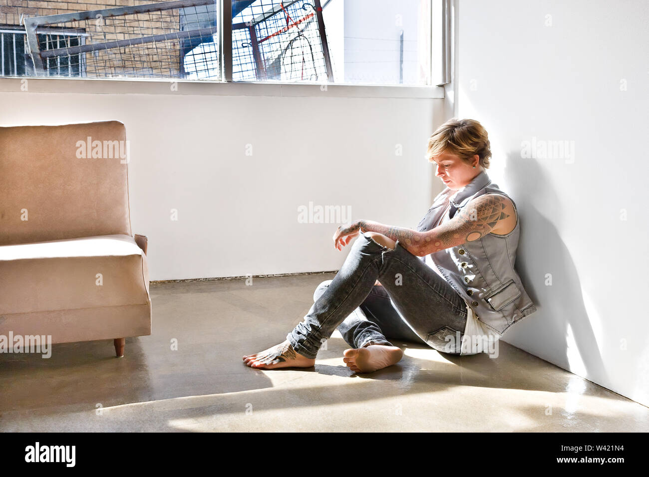 Jeune fille avec un tatouage sur son bras et jambes assis et se courber la tête en bas, comme penser ou montrant la tristesse dans une chambre avec des murs blancs et sous e Photo Stock