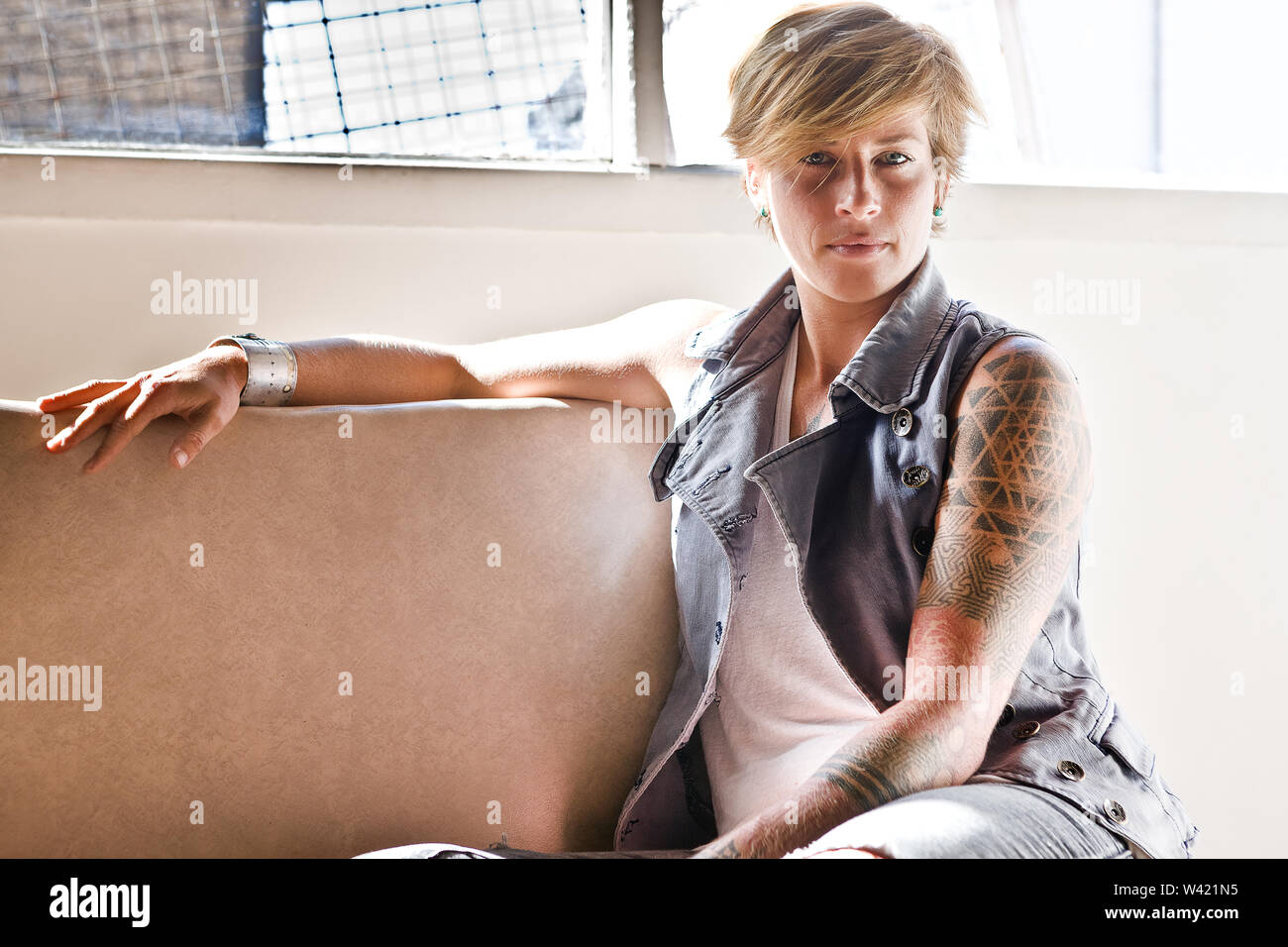 Fille avec un tatouage sur son bras, le regardant assis sur une chaise près de la fenêtre Photo Stock