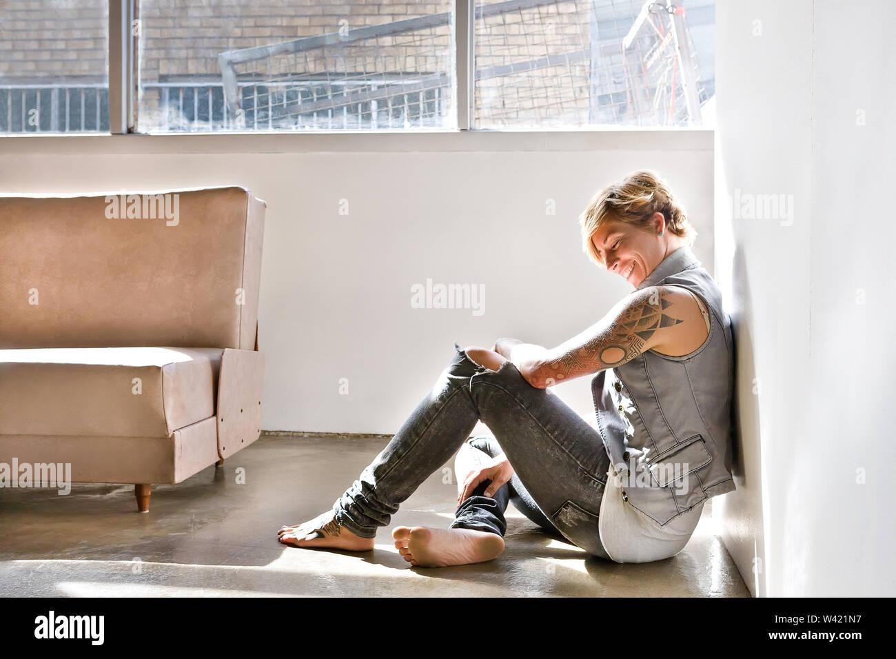 Superbe tatouage à la fille assise sur le sol et souriant près d'un canapé dans une pièce à côté d'une fenêtre qui s'est étendu le soleil Photo Stock