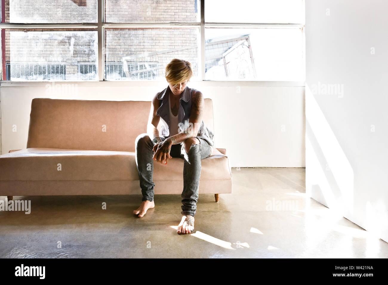 Fille assise sur un canapé et l'air triste dans une pièce blanche qu'éclairé par la lumière du soleil Photo Stock