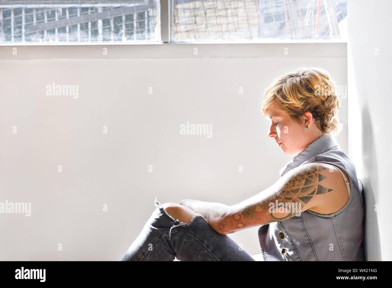 Jolies filles avec des tatouages et une couleur d'or des cheveux plus courts essayer de se concentrer sur un problème s'appuie sur le mur et assis sur le plancher d'une chambre à côté d'une fenêtre Photo Stock