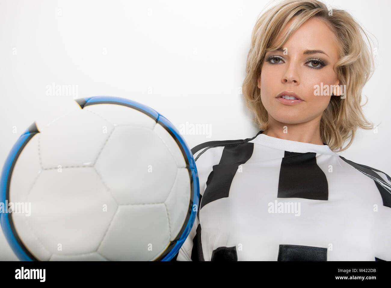 Libre d'un mannequin blond avec un maquillage foncé portant un fan de football jersey et tenant une balle dans un studio avec fond blanc Photo Stock