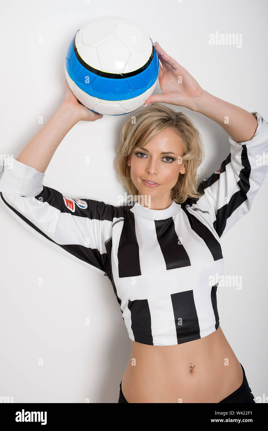 Très jolie jeune femme aux cheveux courts, tenant un ballon de soccer sur sa tête dans un studio avec fond blanc devant un mur blanc dans un noir blanc spor Photo Stock