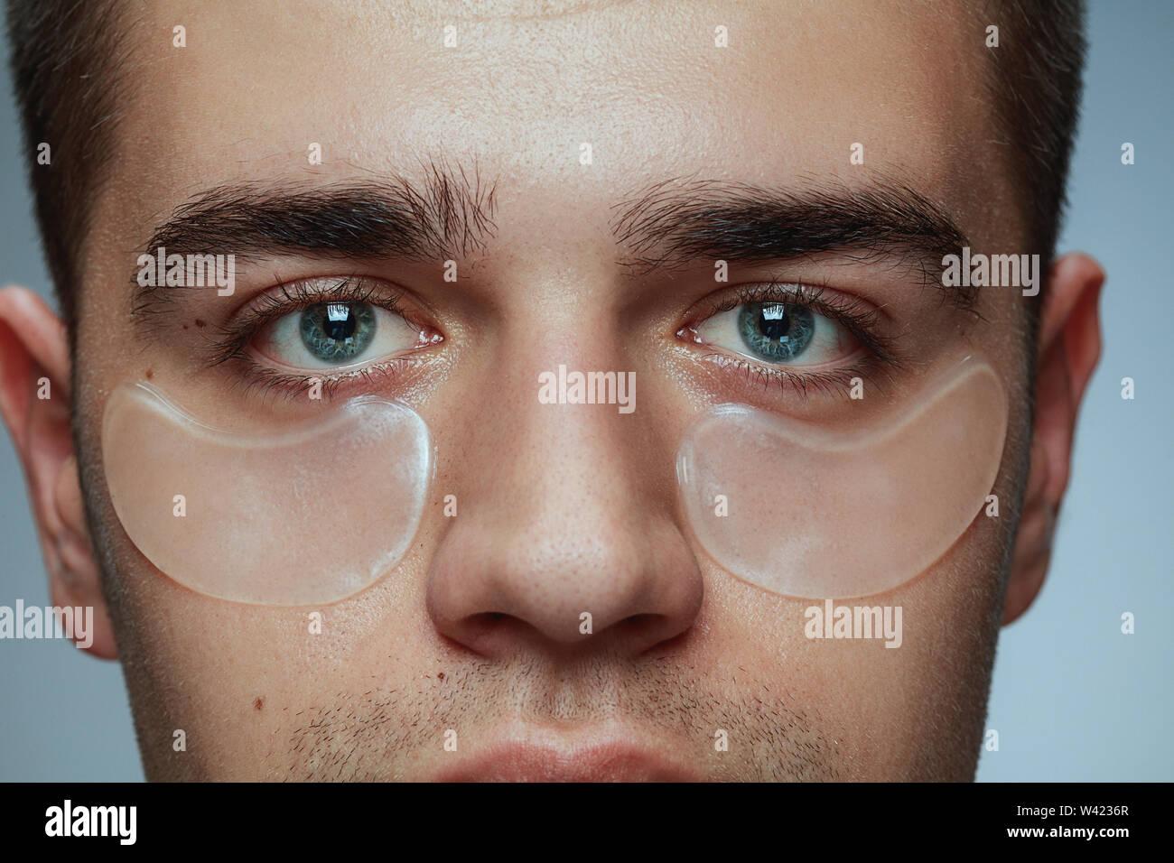 Close-up portrait of young man isolé sur fond studio gris. Visage masculin avec patches collagène sous les yeux. Concept de la santé des hommes et de la beauté, les soins de beauté, soins du corps et de la peau. Anti-vieillissement. Photo Stock