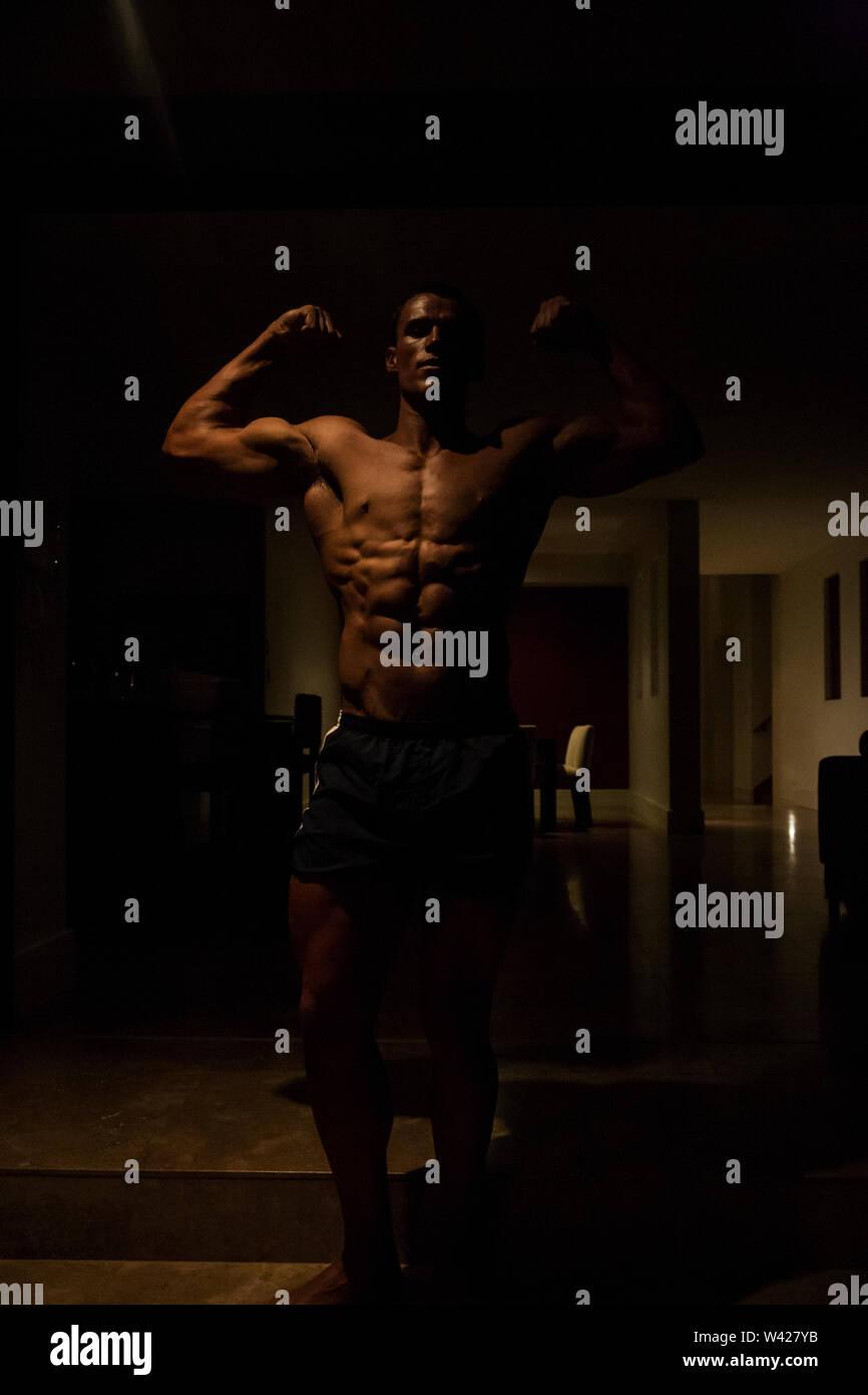 Ultra strong homme faire de l'exercice et se détendre en soirée à la scène à l'intérieur de la chambre d'un hôtel de luxe ou de sport, feux de faible parfait et sombre, quelques dessins et Photo Stock