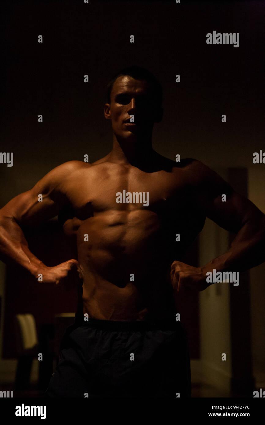 Homme intelligent et profiter de faire de l'exercice, la nuit à l'intérieur de la chambre à la scène d'un hôtel de luxe ou de sport, feux de faible parfait et sombre, quelques dessins et des ombres Photo Stock