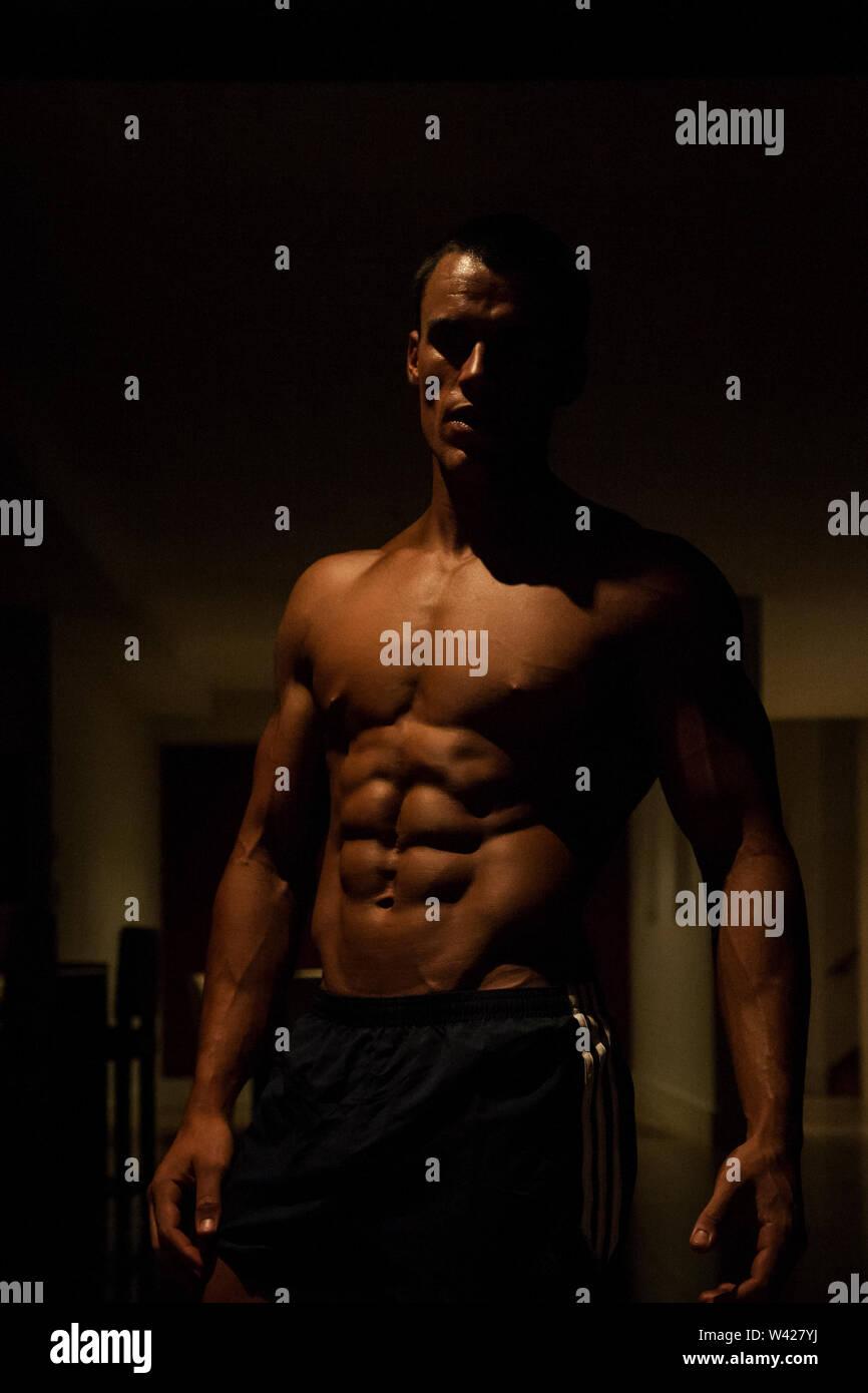 Homme avec six jeux et sain muscels, nuit à l'intérieur de la chambre à la scène d'un hôtel de luxe ou de sport, feux de faible parfait et sombre, quelques dessins et l'ombre Photo Stock