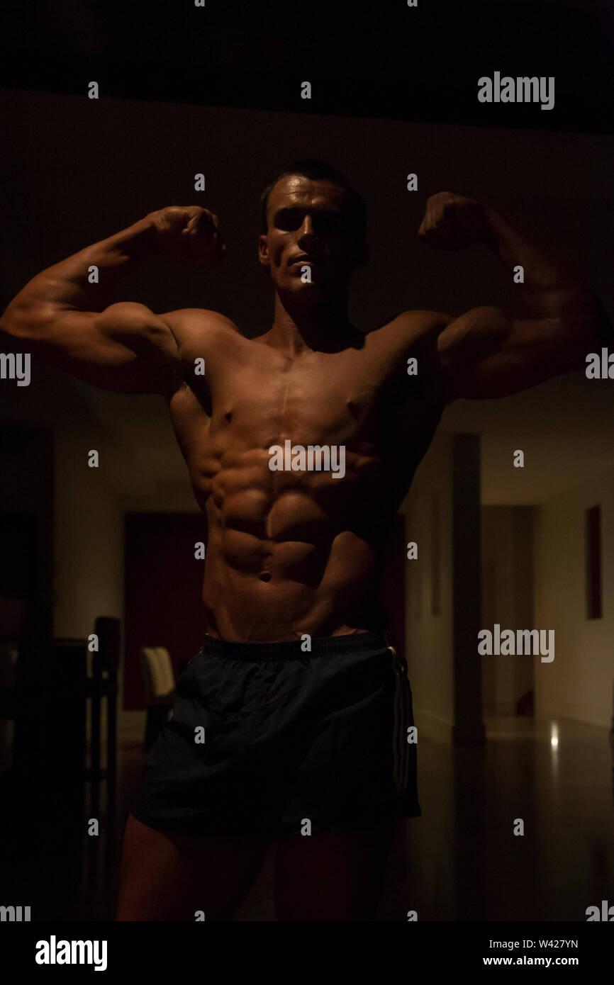 Close up of Body builder avec court noir, nuit à l'intérieur de la chambre à la scène d'un hôtel de luxe ou de sport, feux de faible parfait et sombre, quelques dessins et sha Photo Stock