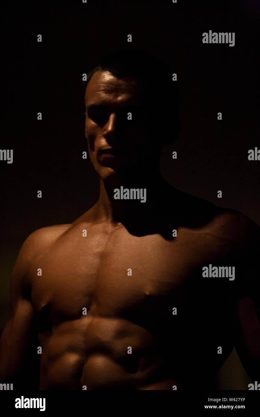 Body builder's six jeux close up, scène de nuit à l'intérieur de la chambre d'un hôtel de luxe ou de sport, feux de faible parfait et sombre, quelques dessins et les ombres peuvent Photo Stock