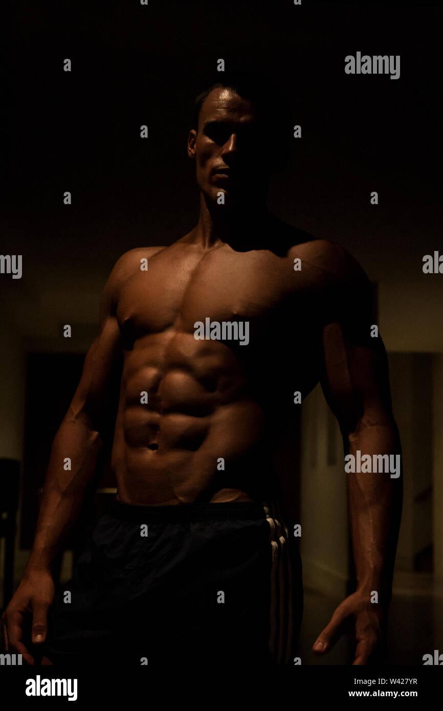Tall Body builder's peau close up, scène de nuit à l'intérieur de la chambre d'un hôtel de luxe ou de sport, feux de faible parfait et sombre, quelques dessins et les ombres peuvent Photo Stock