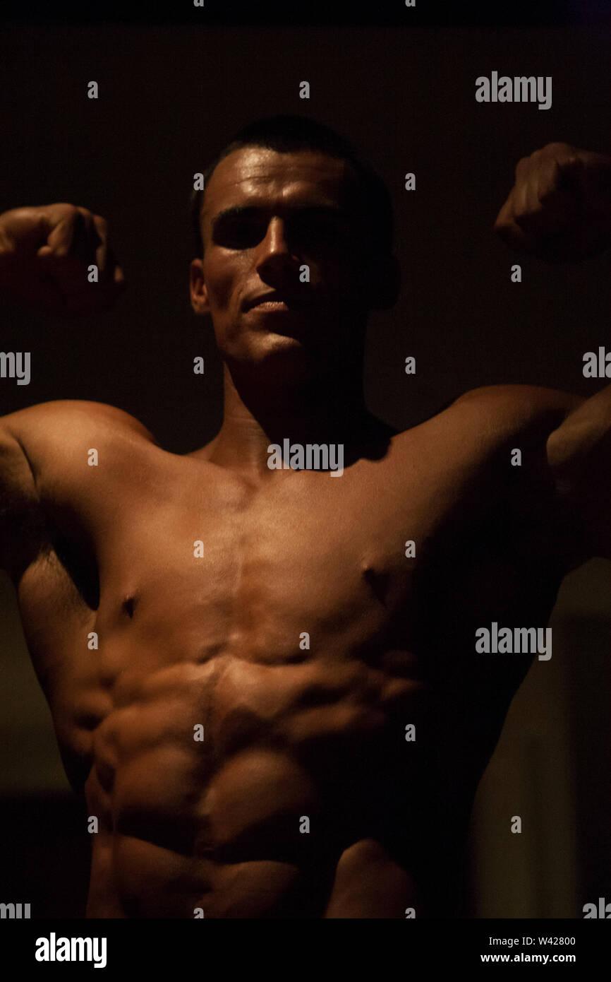 Fitness Trainer's corps sain et muscels, nuit à l'intérieur de la chambre à la scène d'un hôtel de luxe ou de sport, feux de faible parfait et sombre, quelques dessins et sh Photo Stock