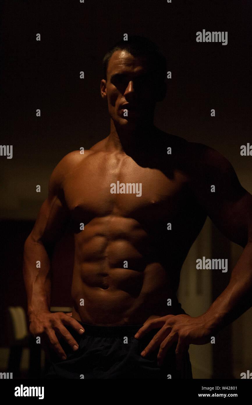 Fitness Trainer avec court noir, nuit à l'intérieur de la chambre à la scène d'un hôtel de luxe ou de sport, feux de faible parfait et sombre, quelques dessins et les ombres peuvent Photo Stock