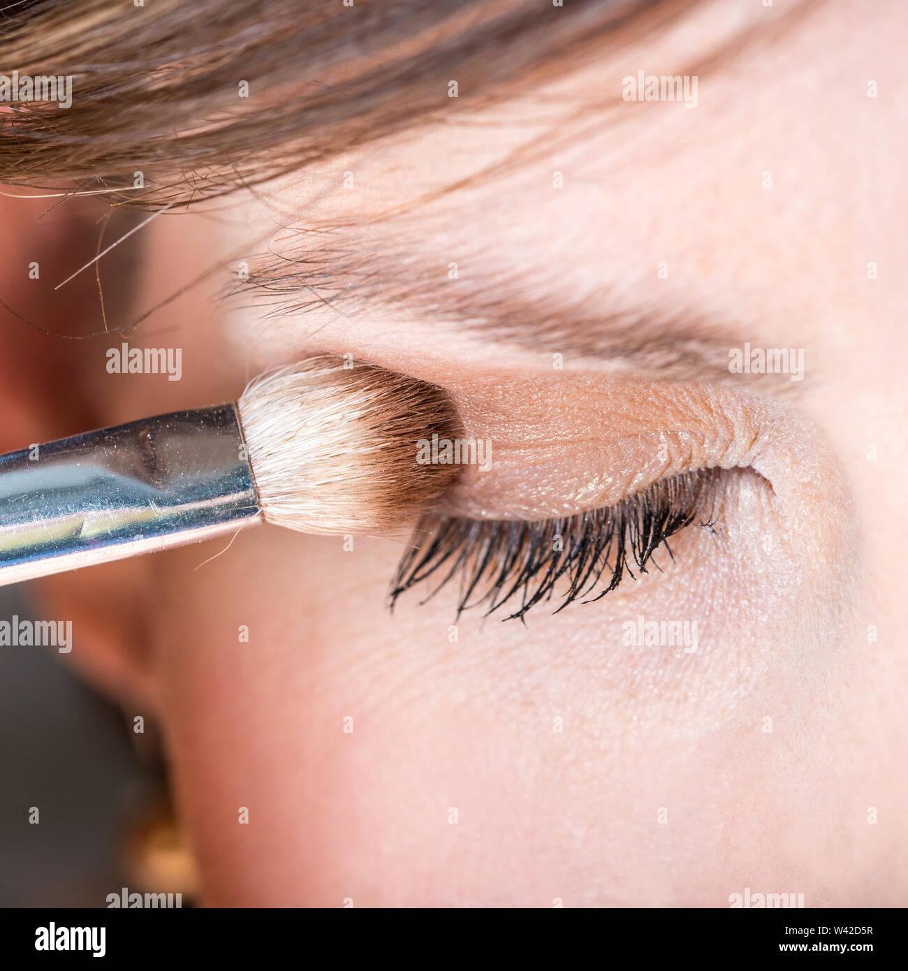Concept de mode et de beauté d'une femme l'application de fard à paupière son avec un applicateur, closeup détail d'un oeil. Photo Stock