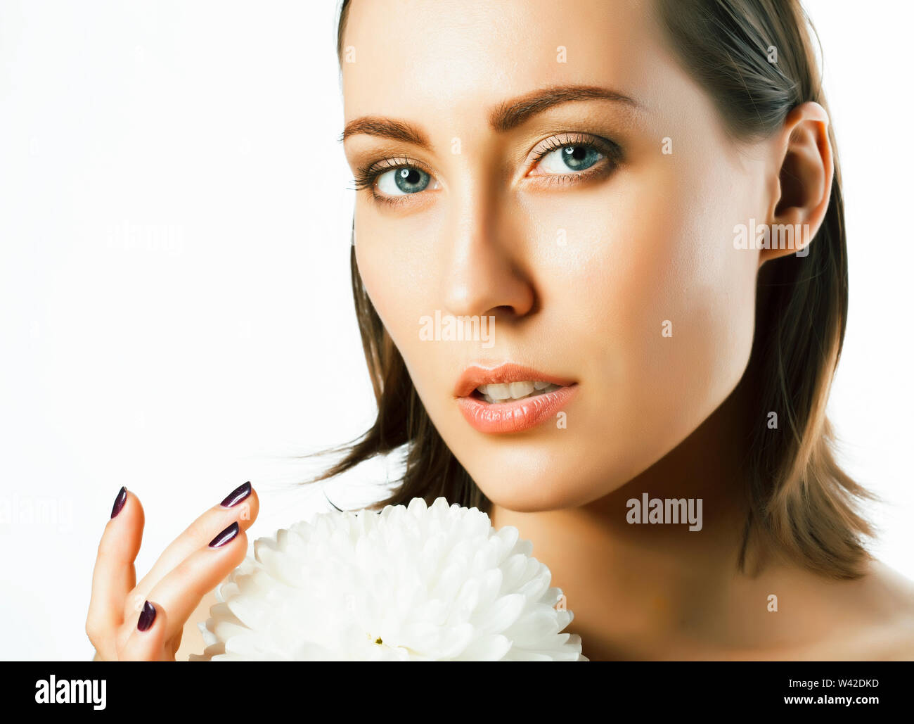 Young pretty caucasian woman with big flower lily spa concept isolated on white closeup Photo Stock