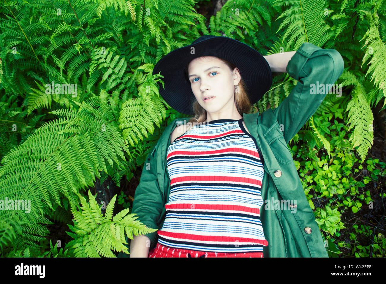 Jolie jeune fille blonde hipster en quête dans la fougère, vacances en forêt verte, style de personnes concept Photo Stock