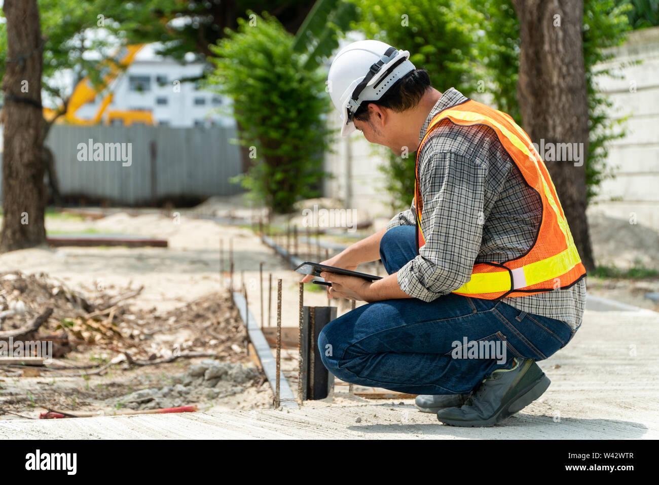 L'ingénierie, portant un casque et holding tablets, s'assoir pour vérifier la structure du couloir dans le parc Banque D'Images