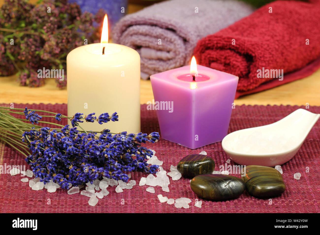 Composition de la lavande séchée, seasalt et massage pierres avec des bougies allumées. Still Life Spa Photo Stock