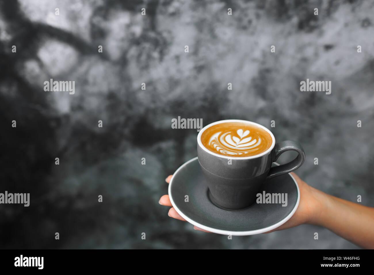 Femme tenant en main tasse de Cappuccino gris sur fond de ciment Mur de béton gris texturé. Hipster tendance design cafe. Banque D'Images