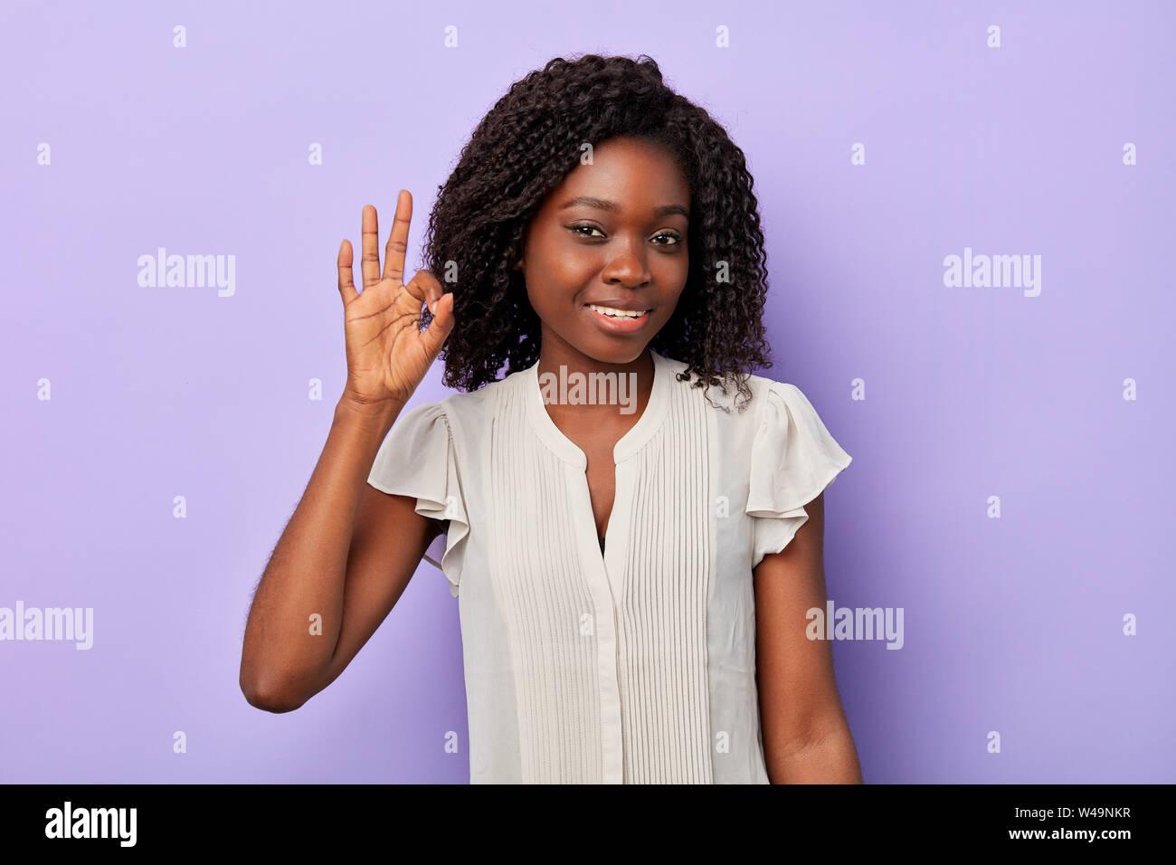 Joli sourire femme afro avec les cheveux bouclés ondulés businesswoman making ok signe, tout est ok. Le langage du corps Banque D'Images