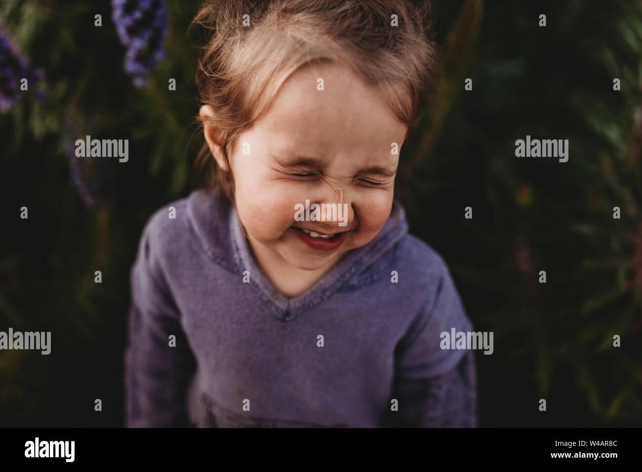 Close up portrait of little girl nez scrunching et rire Banque D'Images