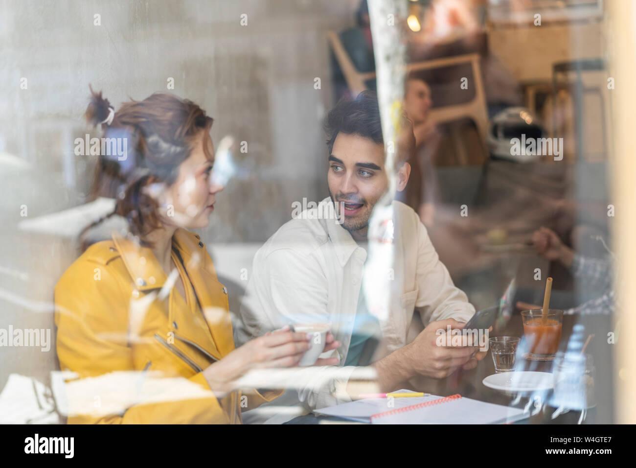 L'homme et la femme avec un téléphone mobile et ordinateur portable dans un café de la réunion Banque D'Images