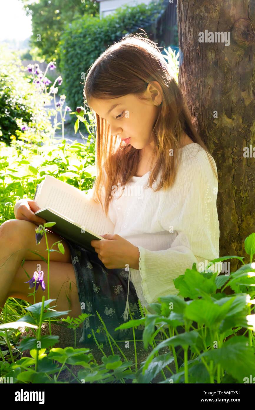 Little girl leaning against tree trunk la lecture d'un livre Banque D'Images