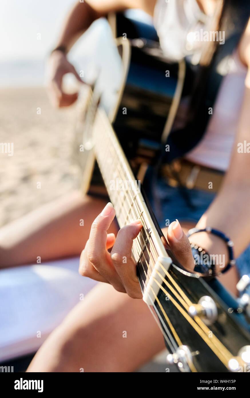 Close-up of young woman playing guitar sur la plage Banque D'Images