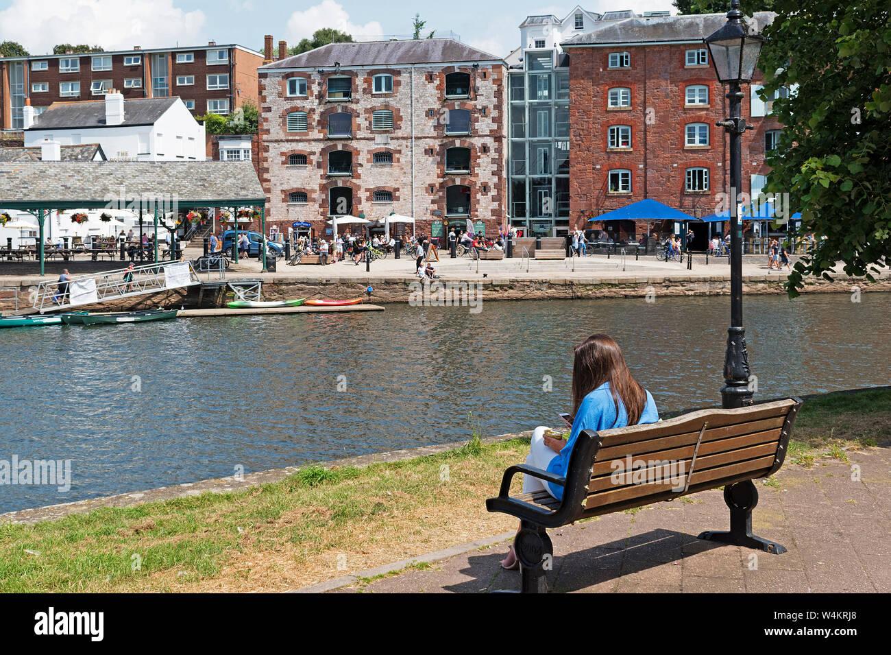 Jeune femme assise sur un banc près de la rivière exe à Exeter, Devon, Angleterre, Grande-Bretagne, Royaume-Uni. Banque D'Images