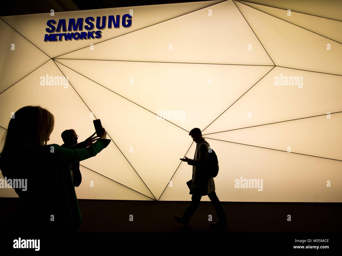 Les visiteurs passent devant le stand de Samsung Networks au cours du Mobile World Congress 2019 (MWC19) à Barcelone, Espagne, 25 février 2019. Banque D'Images