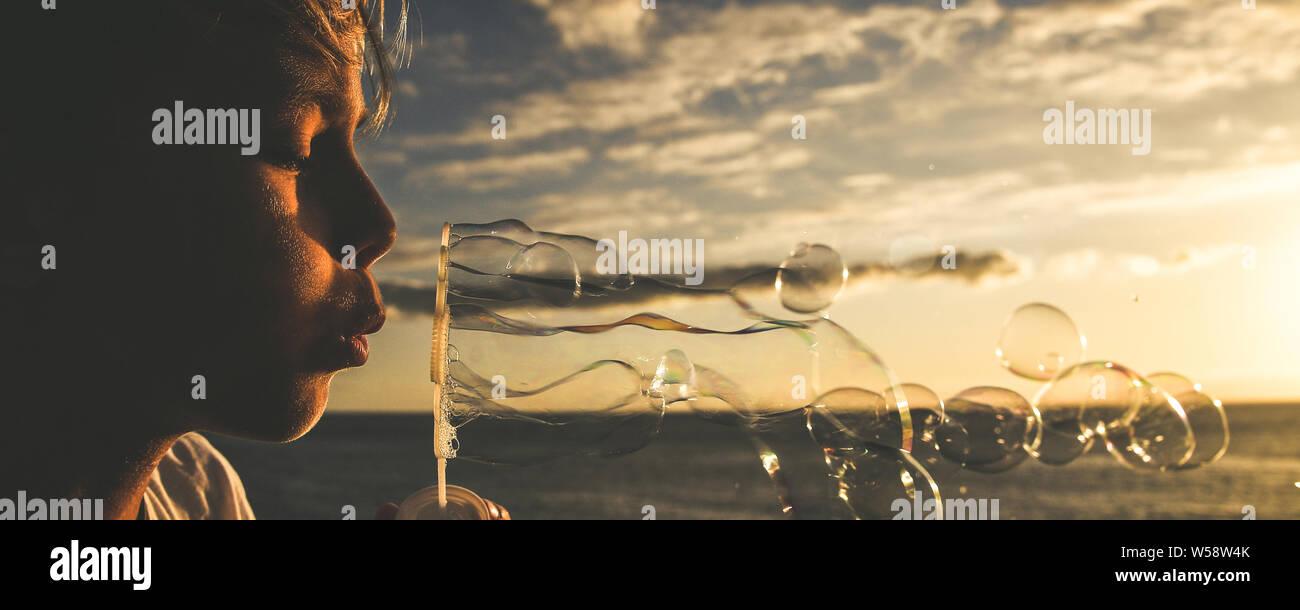 Jeune garçon blond souffle une longue série de bulles dans un champ; l'enfant mignon devant l'océan savon chasse bouillir, beau gosse jouer à l'extérieur dans un magnifique Banque D'Images