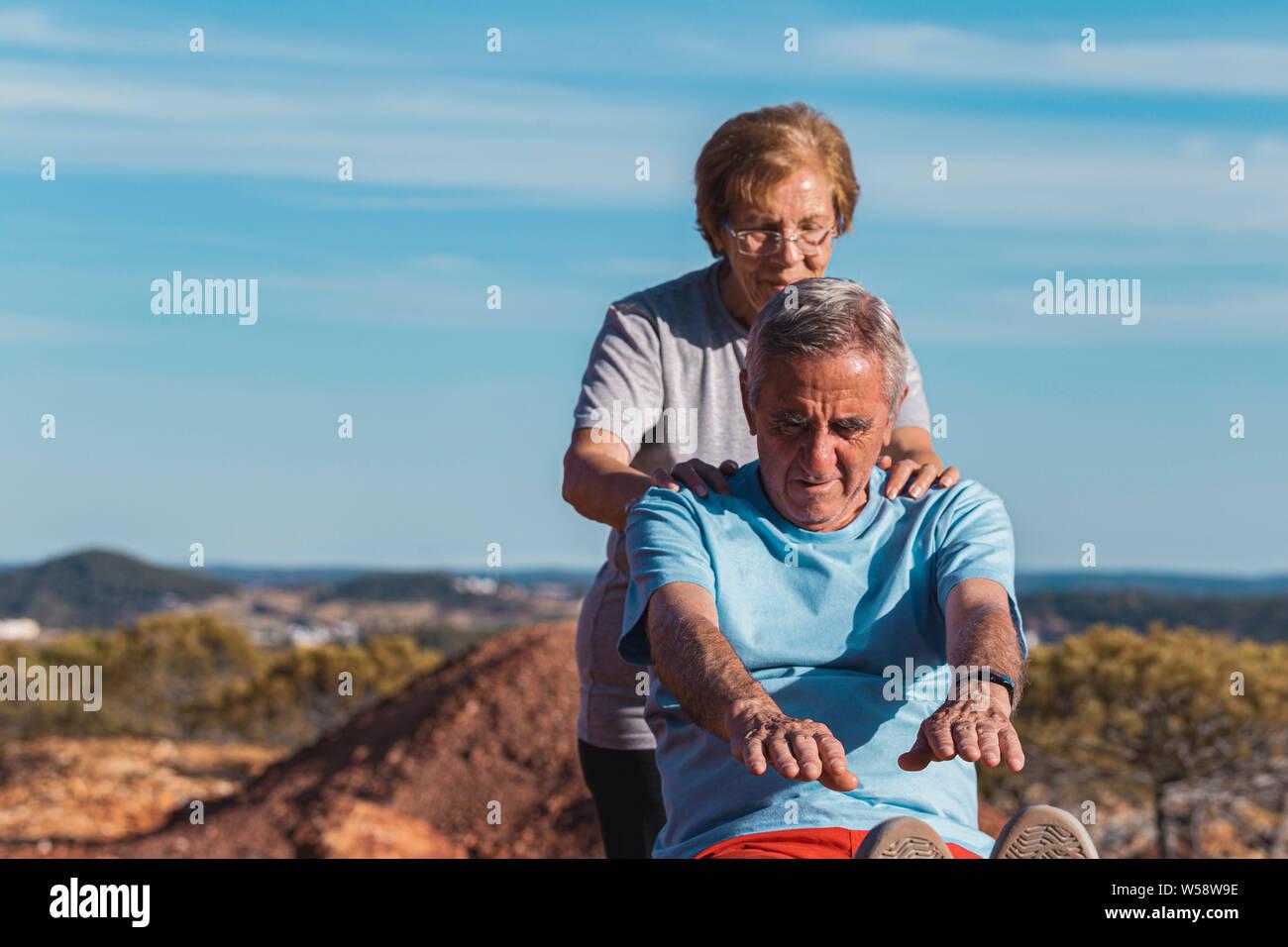 Senior woman aider le vieil homme tout en faisant un exercice s'étendant à l'extérieur avec fond de ciel bleu Banque D'Images